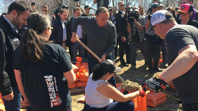 M. Legault pellette du sable dans un sac, entouré de bénévoles, de politiciens et de représentants des médias
