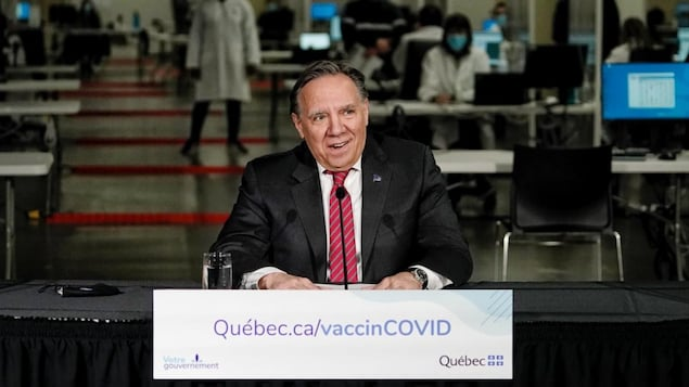 François Legault assis à une table durant un point de presse.
