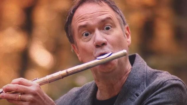 François Pérusse joue de la flûte traversière dans une forêt.