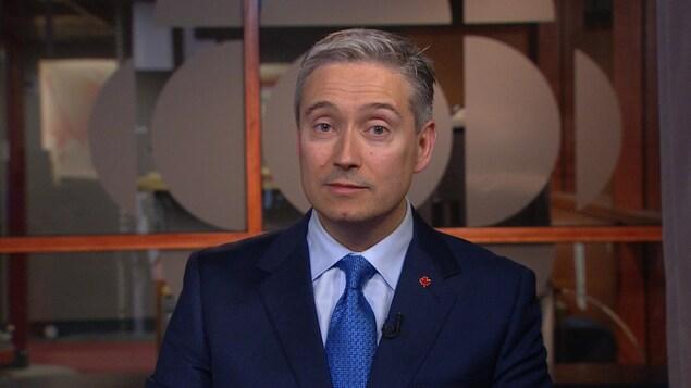 Un homme portant un veston et une cravate regarde droit devant lui. Il est assis devant une vitre sur laquelle se trouve le logo de Radio-Canada.