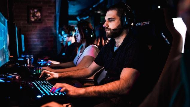 Un homme habillé en noir joue à un jeu vidéo à l'ordinateur à côté d'autres joueurs et joueuses.