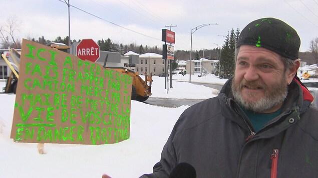 Un homme à côté de la pancarte.