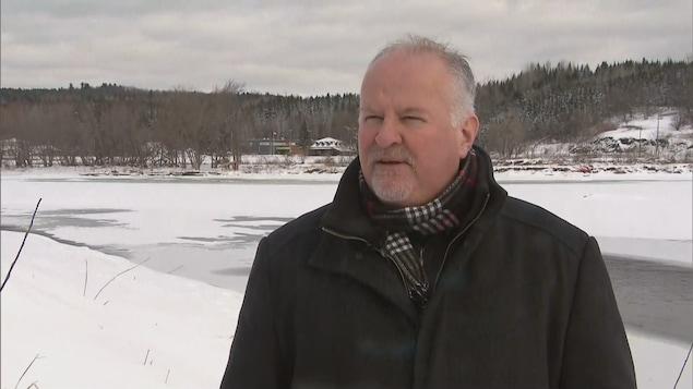 François Veilleux en manteau d'hiver, dehors devant une rivière.