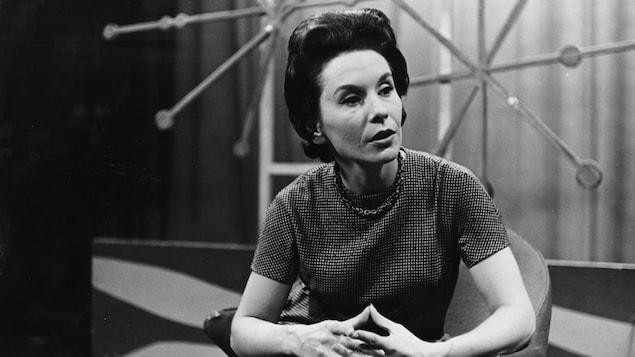 Dans un studio de télévision, la journaliste Françoise Faucher est assise sur une chaise, joignant ses mains devant elle.