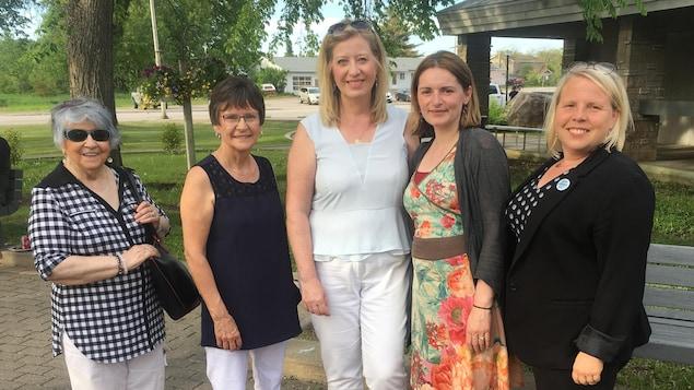 Cinq femmes posant dans un parc.