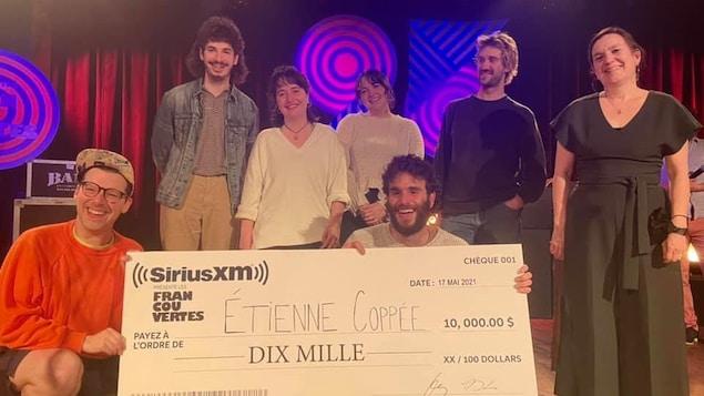 Simon Boulerice et Étienne Coppée, accroupis, tiennent un très grand chèque symbolique sur scène, entourés de plusieurs personnes.