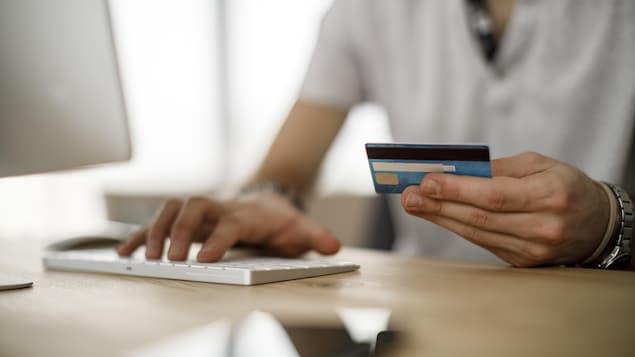 Une personne lit sa carte de crédit devant son ordinateur.
