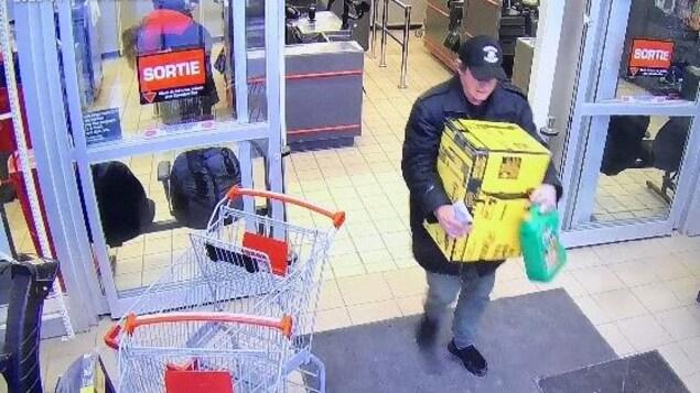 L'homme qui sort d'un commerce avec une boîte.