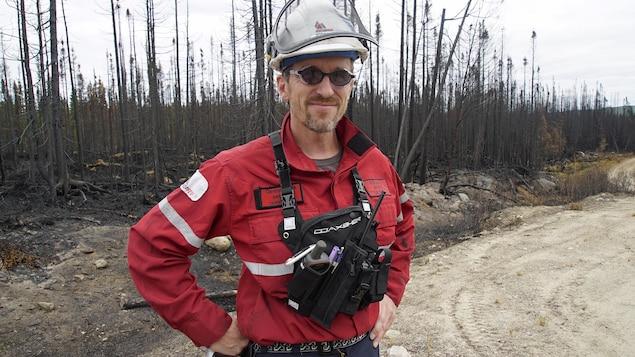 On voit un homme avec un casque et un équipement. Il se trouve sur les lieux d'un incendie de forêt où il s'occupe des opérations. Il s'agit de Frédéric André.