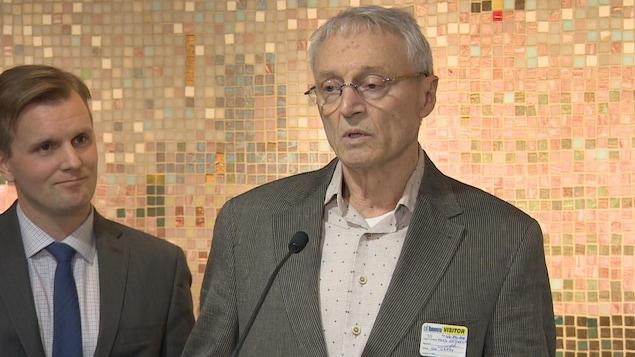 Un homme, plus âgé, devant un micro. À gauche, un homme plus jeune en costume cravate.