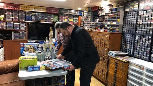 Frédéric Savard dans sa pièce de rangement, entouré de classeurs et de boîtes contenants des pièces de Legos.