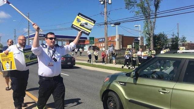 Des ambulanciers marchent le long d'une rue en brandissant des pancartes.