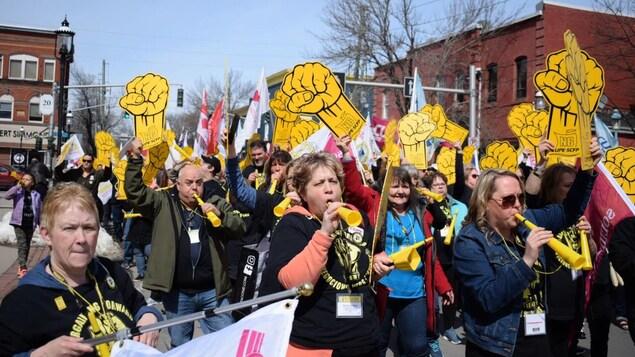 Des dizaines de personnes marchent en brandissant des pancartes syndicales et en soufflant dans des cornets.