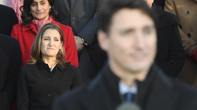 Chrystia Freeland regarde Justin Trudeau parler aux journalistes devant elle.