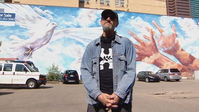 Doug Driediger devant une fresque où deux mains sont tendues vers une colombe en vol.