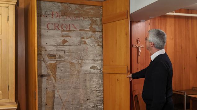 Un homme ouvre un panneau de bois qui donne sur une vieille fresque majoritairement effacée