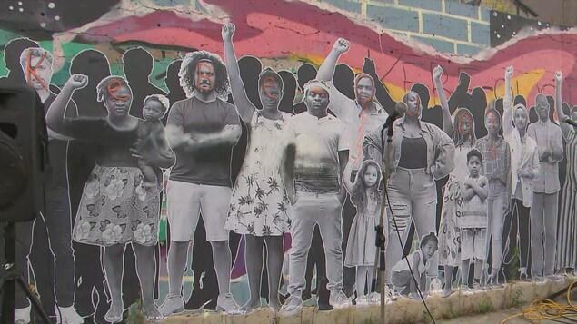 Une fresque murale représentant des personnes de couleur dont le visage a été gribouillé.