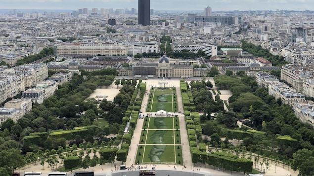Des mains entrelacées peintes sur le gazon, et en arrière-plan, la ville de Paris.