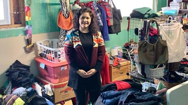 Une femme entourée de vêtements dans une friperie dans son sous-sol.