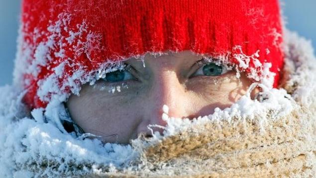 Une femme avec une tuque glacée et de la glace sur ses cils.