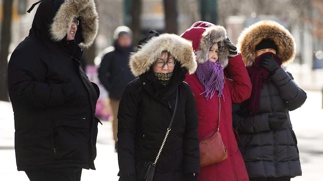 Trois femmes et un homme qui grelottent dehors au coin d'une rue, malgré leur gros manteau d'hiver.