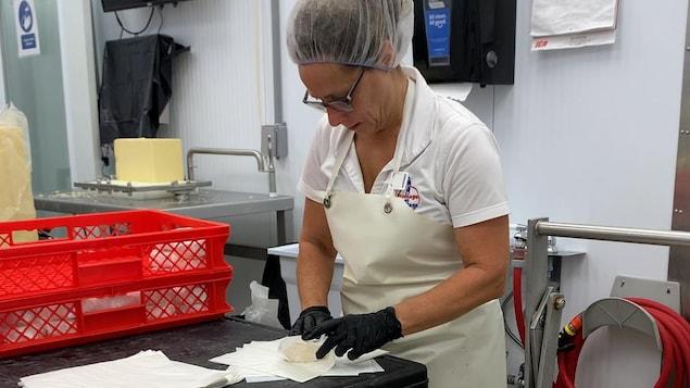 Une femme emballe un fromage.