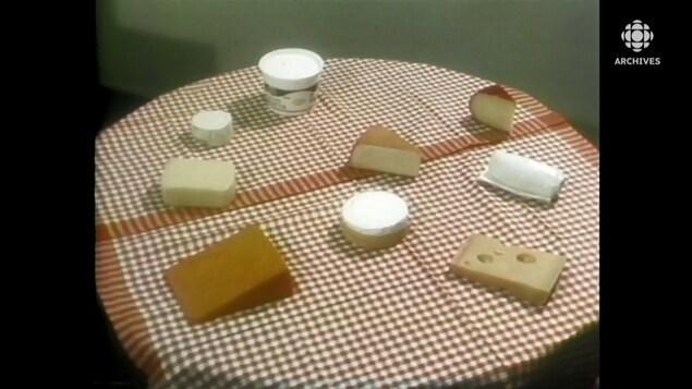 Des morceaux de fromage sont présentés sur une table ronde décorée d'une nappe Vichy.