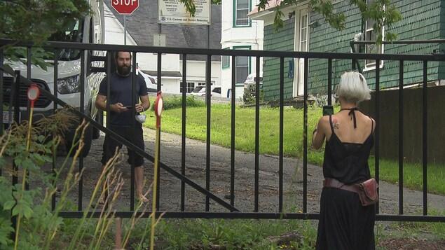 Le couple discute au travers d'une barrière.