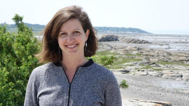 Karine Vincent sourit devant le fleuve Saint-Laurent.