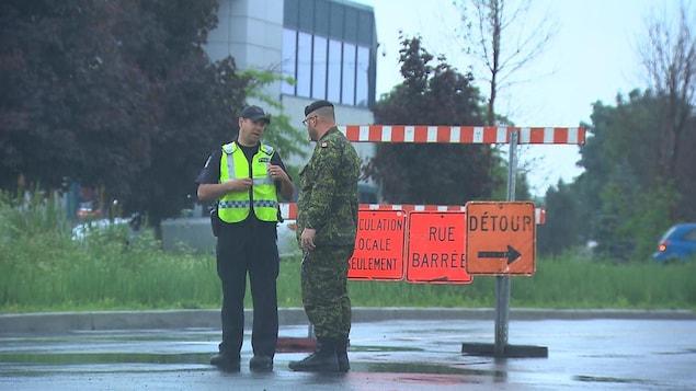 Un policier et un militaire discutent devant des panneaux indiquant qu'une rue est barrée.