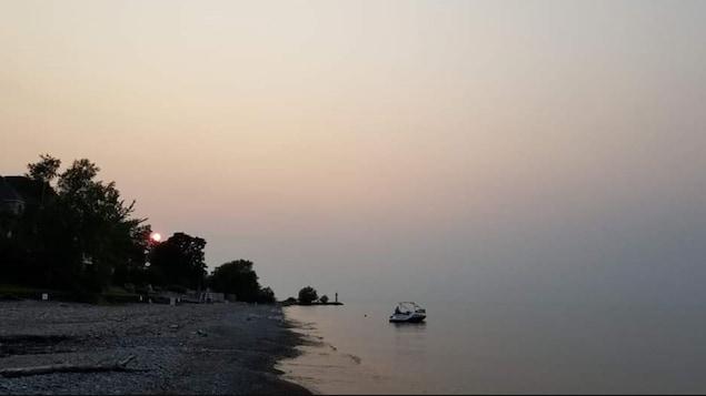 De la fumée est visible dans l'air près d'un lac.