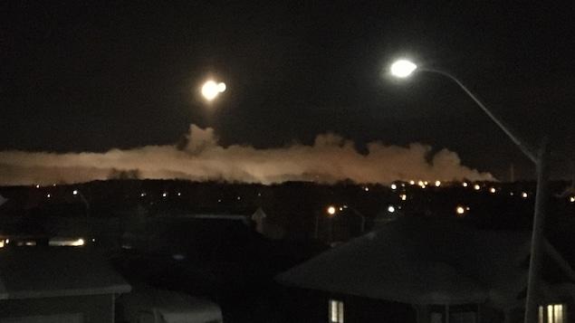 Da la fumée blanche se répand dans le ciel au-dessus du toit des maisons.