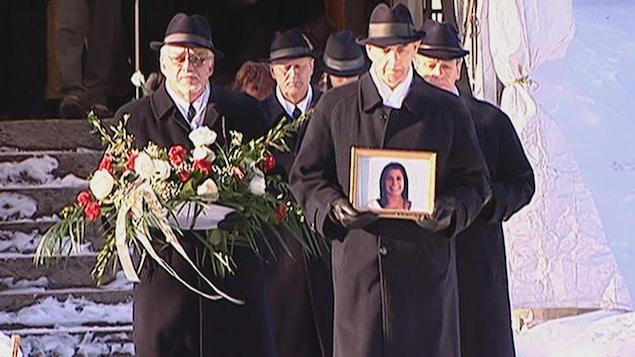Des hommes transportant une gerbe de fleurs et une photo de Mélissa Lambert sortent de l'église.