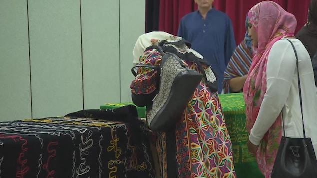 Une femme avec un foulard pleure sur un cercueil.