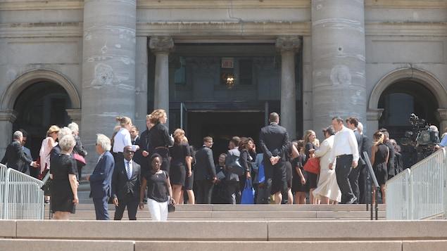 Des dizaines de personnes discutent sur le parvis de la cathédrale-basilique, en plein soleil.