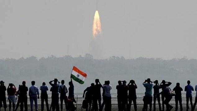 Une photo montre une foule qui observe une fusée décollée à proximité de la station spatiale de Sriharikota en Inde. secteur spatial canadien don't let go canada