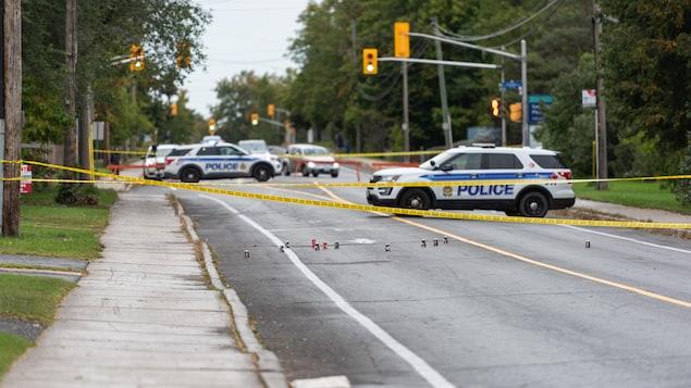 Des rubans jaunes et des voitures de police sur une scène de crime.