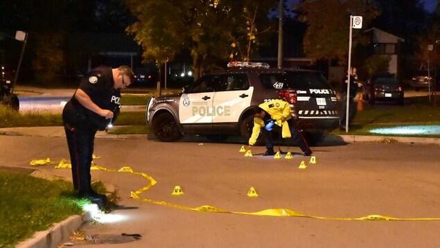 Des policiers relèvent des indices dans la rue