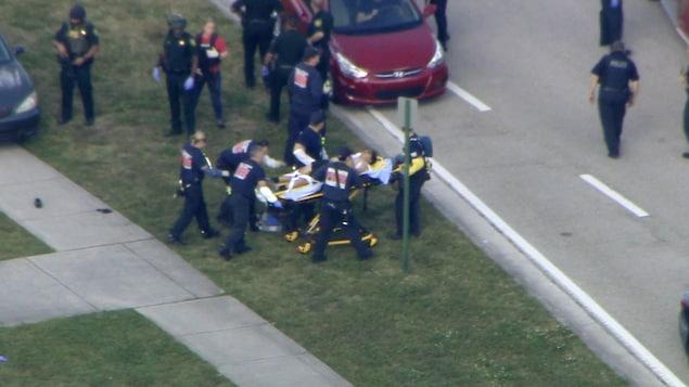 Dans cette capture d'écran fournie par WPLG-TV, le personnel d'urgence évacue une personne blessée de l'école secondaire Marjory Stoneman Douglas à Parkland, en Floride.