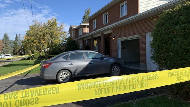 Une voiture stationnée devant une résidence de banlieue, à l'intérieur d'un périmètre policier.
