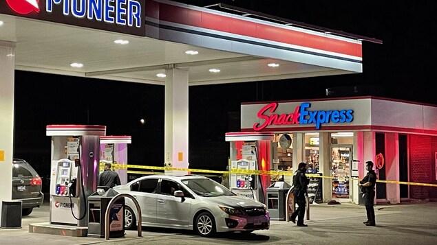 Station d'essence la nuit entourée d'un ruban jaune de la police. Deux policiers se trouvent près des installations.
