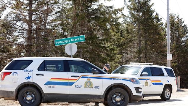 Deux véhicules de la GRC stationnés près d'une intersection pour bloquer la route.
