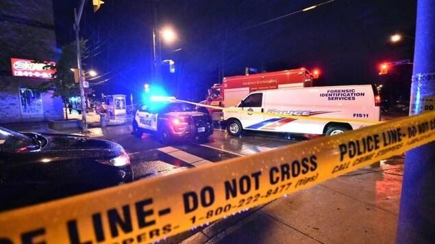 Une scène de crime, la nuit, entourée du ruban jaune de police. Plusieurs véhicules d'urgence sont sur place.