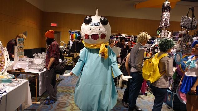 Une femme est dans un costume dont la tête est faite en papier mâché et porte une robe bleu ciel et des gants blancs.