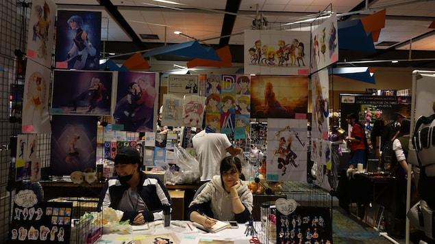 Roxane Danault est assise à son kiosque tandis que l'on voit des œuvres de manga qu'elle a elle-même dessinées.