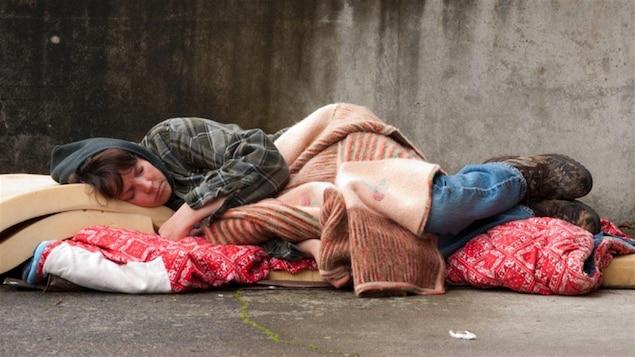 Une femme sans-abri dort par terre.