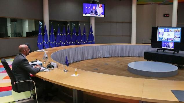 Charles Michel, président du Conseil européen, assis à une table vide devant un écran.
