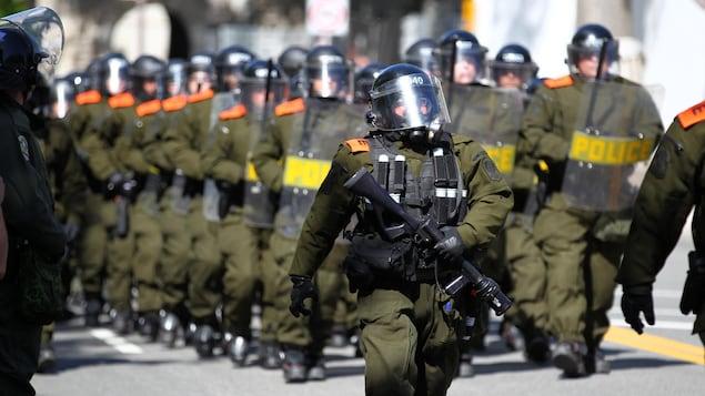 Des policiers en uniforme vêtus de masques à gaz