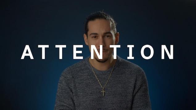 Gabriel Thibert regarde la caméra. Le mot ATTENTION est superposé sur l'image.