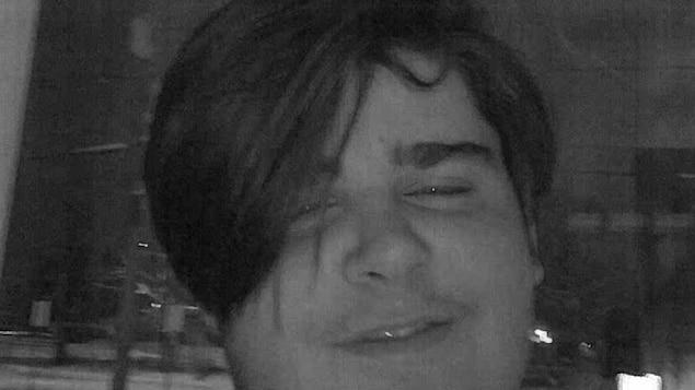 Un adolescent sourit à la caméra.